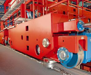 Wheel sets with lateral guide rollers, driven by Demag offset geared motors on a double-girder overhead travelling crane